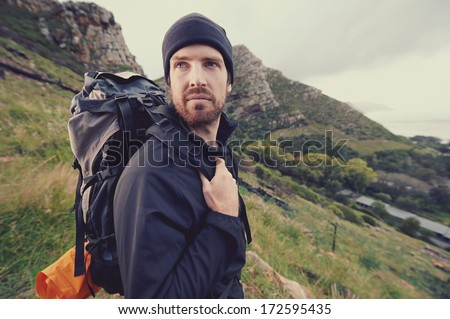 Portrait of adventure trekking man in mountains with backpack - stock photo