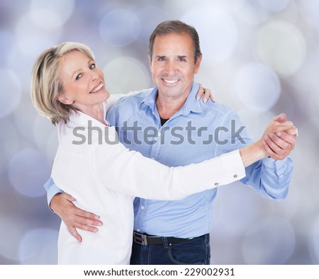 Portrait of affectionate couple dancing against colored background - stock photo