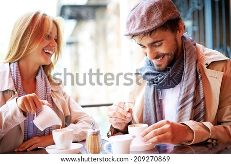 Portrait of affectionate couple in stylish clothes having coffee in cafe - stock photo
