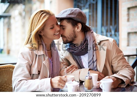 Portrait of affectionate couple in stylish clothes spending time in cafe - stock photo