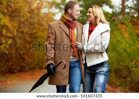 Portrait of affectionate couple taking a walk in autumnal park - stock photo