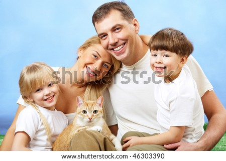 Portrait of affectionate family members looking at camera on blue background - stock photo