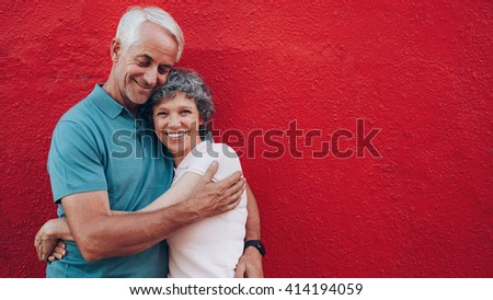 Portrait of affectionate mature couple embracing each other against red background and smiling. Senior couple against red wall with copy space. - stock photo