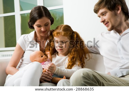 Portrait of affectionate parents and their daughter sitting on sofa at home - stock photo