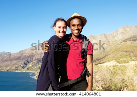 Portrait of affectionate young couple on summer vacation standing together outdoors on a mountain - stock photo