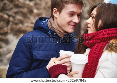 Portrait of affectionate young dates having coffee from plastic glasses outside  - stock photo