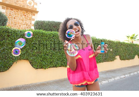 Portrait of african american black teenager girl having fun on a summer day blowing bubbles in a suburban street, holiday lifestyle outdoors. Adolescent young woman active living, home exterior. - stock photo