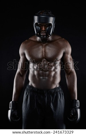 Portrait of african american boxer wearing protective gear standing on black background. Muscular young man in boxing gear. - stock photo