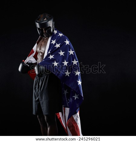 Portrait of african american Boxer with the American flag draped around his body against black background - stock photo