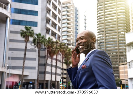 Portrait of african american business man talking on mobile phone in the city - stock photo