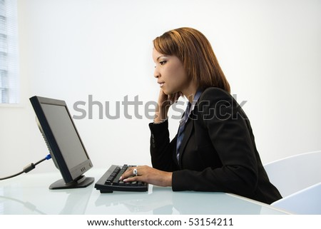 Portrait of African American businesswoman sitting at office desk working on computer. - stock photo