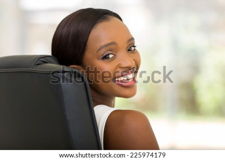 portrait of african american businesswoman sitting in office - stock photo