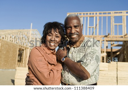 Portrait of African American couple in front of new home still under construction - stock photo