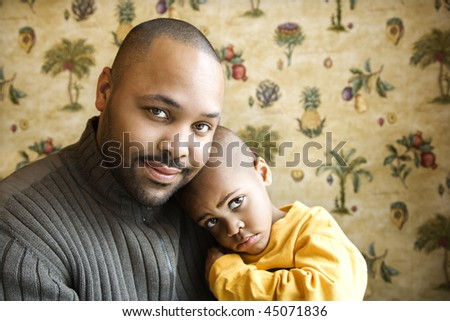 Portrait of african american father holding his young son and looking at viewer.  Horizontal shot. - stock photo