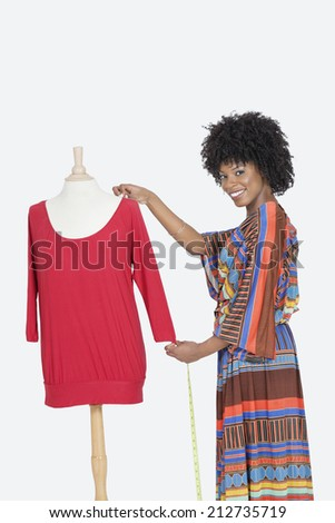Portrait of African American female designer measuring a red tunic over gray background - stock photo