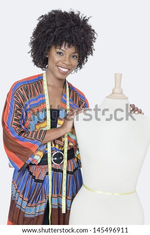 Portrait of African American female fashion designer with tailor's dummy over gray background - stock photo