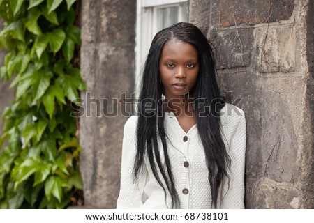 Portrait of African American female standing against stone wall - stock photo