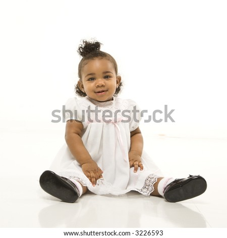 Portrait of African American infant girl sitting against white background.