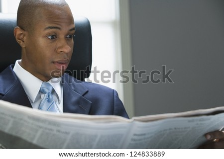 Portrait of African American man reading newspaper - stock photo