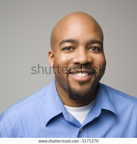Portrait of African American man smiling against gray background. - stock photo