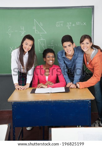 Portrait of African American teacher with teenage students at desk in classroom - stock photo