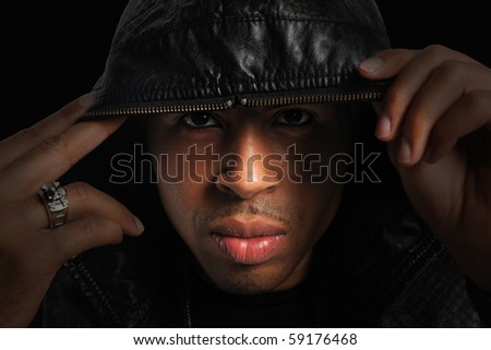 Portrait of African American with hood over head with strong directional light - stock photo