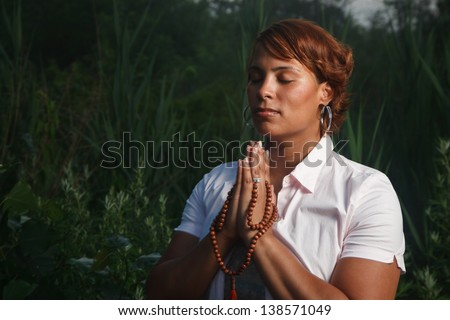 Portrait of African American woman praying outdoors at night. - stock photo