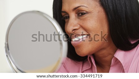 Portrait of African American woman smiling at a mirror - stock photo
