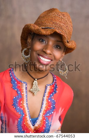 Portrait of African American woman wearing hat and smiling - stock photo