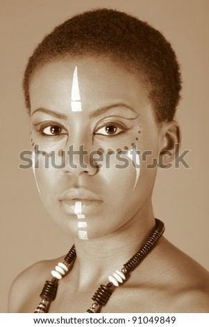 Portrait of African American woman wearing original tribal themed face-paint and necklace - stock photo