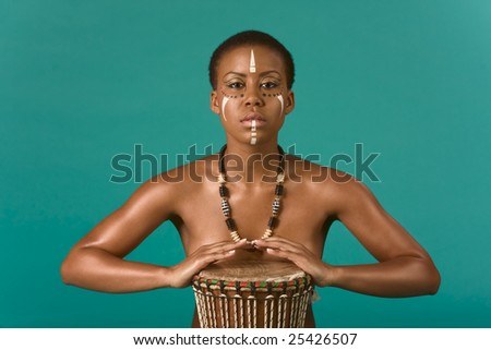 Portrait of African American woman wearing original tribal themed face-paint and necklace playing Conga drum - stock photo