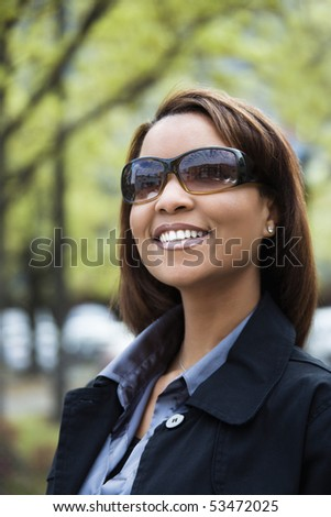 Portrait of African American woman wearing sunglasses and smiling. - stock photo