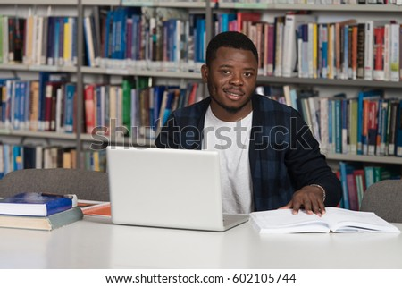 Portrait Of African Clever Student With Open Book Reading It In College  Library   Shallow Depth