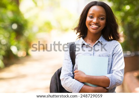 portrait of african college student holding a book - stock photo