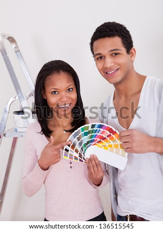 Portrait Of African Couple Choosing Color For New Home - stock photo
