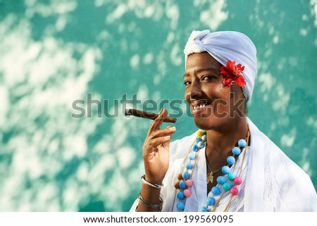 Portrait of african cuban woman smoking cohiba cigar and looking at camera smiling  - stock photo