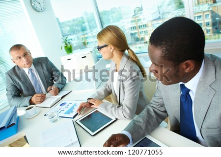 Portrait of African employee and secretary looking at boss while discussing new project at meeting - stock photo