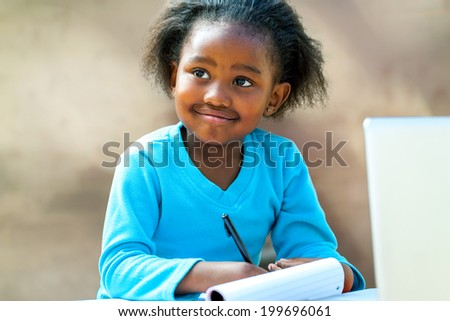Portrait of African girl writing in notebook at desk.