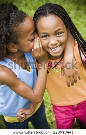 Portrait of African girls telling secret - stock photo