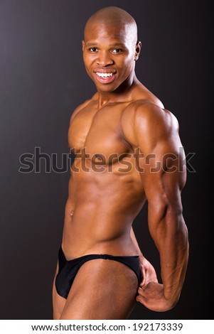 portrait of african male bodybuilder flexing muscles - stock photo