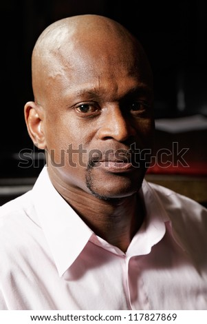 Portrait of african man in pink shirt looking to camera - stock photo