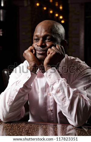 Portrait of african man in pink shirt sitting at desk leaning on fists - stock photo