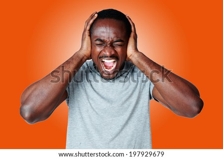 Portrait of african man shouting and closing ear by his hands on orange background - stock photo