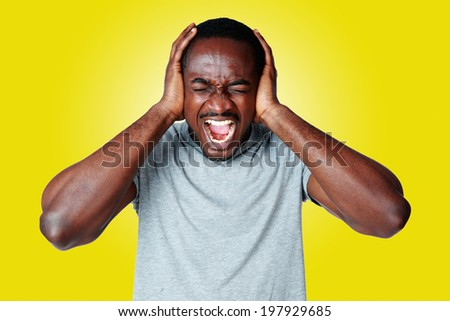 Portrait of african man shouting and closing ear by his hands on yellow background - stock photo