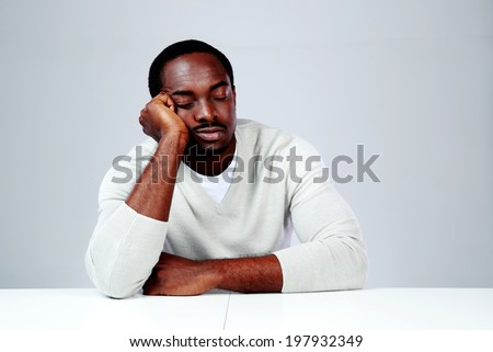 Portrait of african man sleaping at his workplace on gray background - stock photo