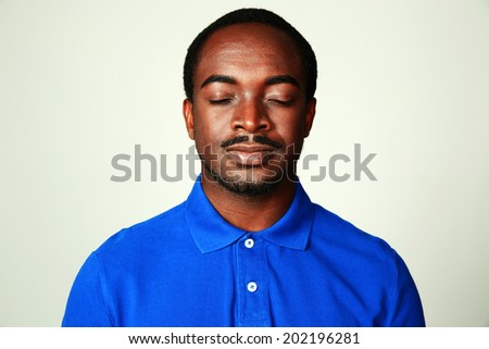Portrait of african man with eyes closed isolated on gray background - stock photo