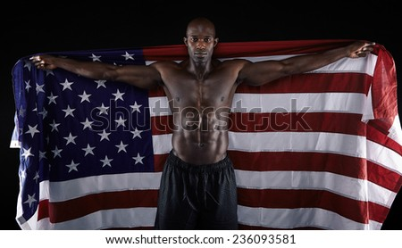 Portrait of african muscular male holding American Flag against black background. Masculine shirtless young man holding United States of American flag. - stock photo
