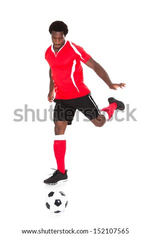 Portrait Of African Soccer Player Kicking Football Over White Background - stock photo