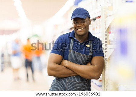 portrait of african supermarket worker with arms folded - stock photo
