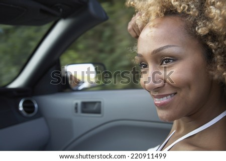Portrait of African woman in convertible car - stock photo